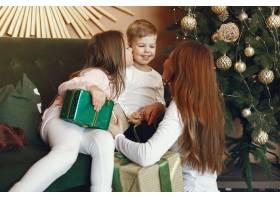 母亲在圣诞树附近带着可爱的孩子_9659205