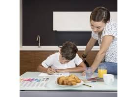 母亲在家里检查儿子的绘画_9423141