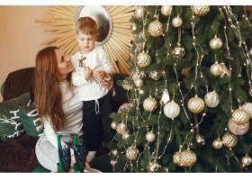 母亲带着可爱的儿子在圣诞树附近_9659186