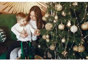 母亲带着可爱的儿子在圣诞树附近_9659190