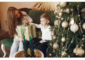 母亲带着可爱的儿子在圣诞树附近_9659192