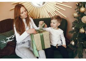 母亲带着可爱的儿子在圣诞树附近_9659194