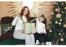 母亲带着可爱的儿子在圣诞树附近_9659196