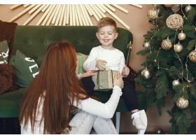母亲带着可爱的儿子在圣诞树附近_9659198
