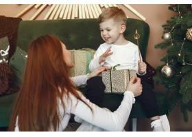 母亲带着可爱的儿子在圣诞树附近_9659200