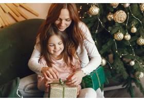 母亲带着可爱的女儿在圣诞树附近_9659207
