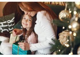 母亲带着可爱的女儿在圣诞树附近_9659210