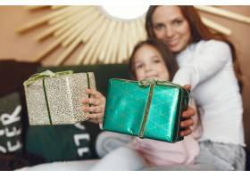 母亲带着可爱的女儿在圣诞树附近_9659212