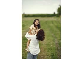 母亲带着女儿在夏日田野里玩耍_9658676