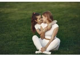 母亲带着女儿坐在草地上_9695906