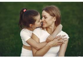 母亲带着女儿坐在草地上_9695911