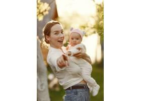 母亲带着她的婴儿在夏日花园里消磨时间_9343709