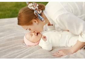 母亲带着她的婴儿在夏日花园里消磨时间_9343713