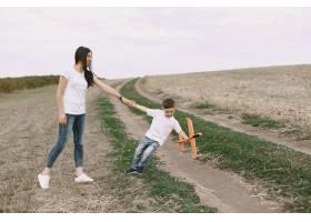 母亲带着小儿子玩玩具飞机_9696210