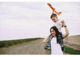 母亲带着小儿子玩玩具飞机_9696220
