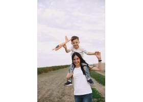 母亲带着小儿子玩玩具飞机_9696222