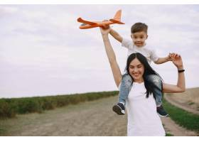 母亲带着小儿子玩玩具飞机_9696224