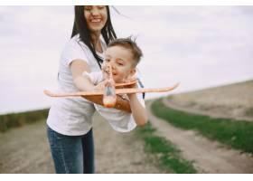母亲带着小儿子玩玩具飞机_9696226