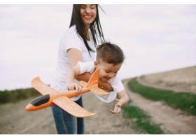 母亲带着小儿子玩玩具飞机_9696228
