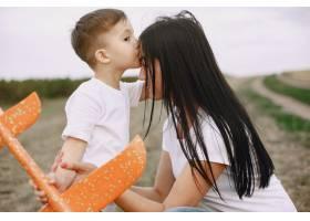 母亲带着小儿子玩玩具飞机_9696235