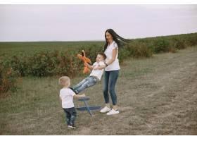 母亲带着小儿子玩玩具飞机_9696252