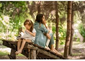 年轻的母女俩在公园的一座木桥上读了一本书_10107370