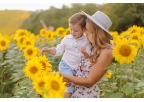 幸福的年轻家庭母亲父亲和儿子在向日_9409621