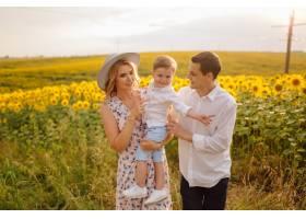 幸福的年轻家庭母亲父亲和儿子在向日_9409645