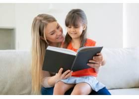 开朗的妈妈和她的黑发女孩在家一起看书_9988374