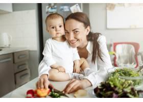 微笑快乐的母亲带着她的孩子在厨房里摆姿势_9696777