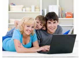 微笑的家庭使用笔记本电脑_10012604