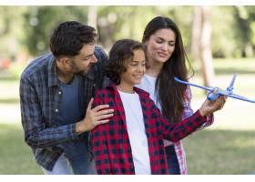 微笑的父母和孩子一起在户外玩飞机_9860918