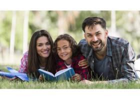 微笑的父母和孩子在一起阅读_9860922