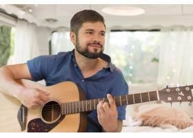 微笑的男人在他的大篷车里弹吉他_9943136