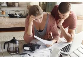 忧心忡忡的夫妇审查他们的家庭财务状况并计_9957095