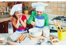 快乐的两个有趣的孩子正在厨房里准备面团_9480427