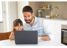 快乐的女孩和她的爸爸使用笔记本电脑坐在_9988521
