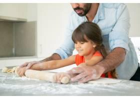 快乐的女孩和她的爸爸在厨房桌子上滚面团_9988520