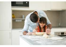 快乐的女孩和她的爸爸在厨房里一边滚一边揉_9988555