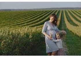 怀孕的母亲带着女儿在田里_9659053