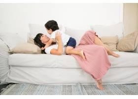 快乐的年轻黑发妈妈躺在沙发上用爱拥抱着_9988547