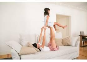 快乐的母亲躺在沙发上和女儿玩耍_9988536