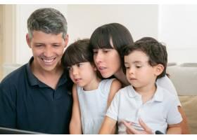 快乐的父母和两个孩子一起看着电脑显示器_9988542