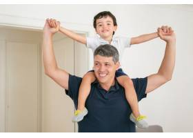 快乐的爸爸把儿子抱在肩上双手张开_9988485