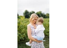 快乐的金发女人和可爱的小男孩站在夏日花园_9409153