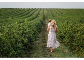 快乐的金发女人和可爱的小男孩站在夏日花园_9409179