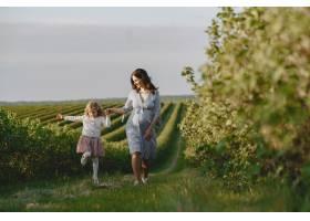 怀孕的母亲带着女儿在田里_9659060