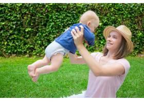 戴着帽子的漂亮妈妈带着新生儿玩耍微笑着_9648870
