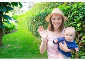 戴着帽子的美丽母亲挥手抱着新生儿微笑_9648877