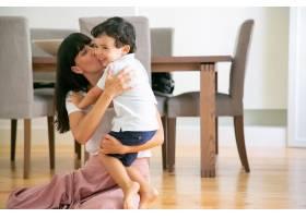 年轻漂亮的母亲坐在地板上亲吻儿子_9988313